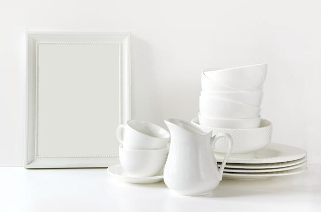 Louças, prato, utensílios e outras coisas brancas diferentes sobre a mesa branca.