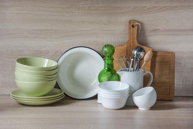 Louças, talheres, utensílios e outras coisas diferentes em cima da mesa de madeira.