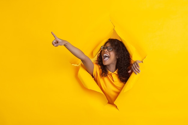 Louco feliz apontando. jovem afro-americana alegre em fundo de papel amarelo rasgado, emocional, expressivo. rompendo, descoberta. conceito de emoções humanas, expressão facial, vendas, anúncio.
