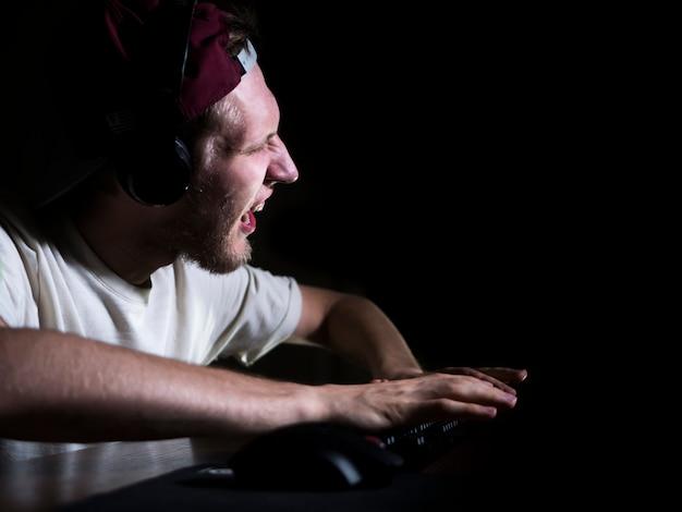 Louco viciado em jogo louco jogando videogame no meio da noite em casa.