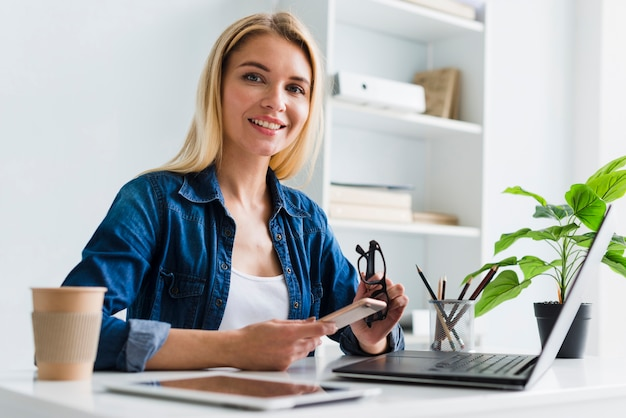 Loura, mulher trabalhadora, segurando, smartphone, e, óculos