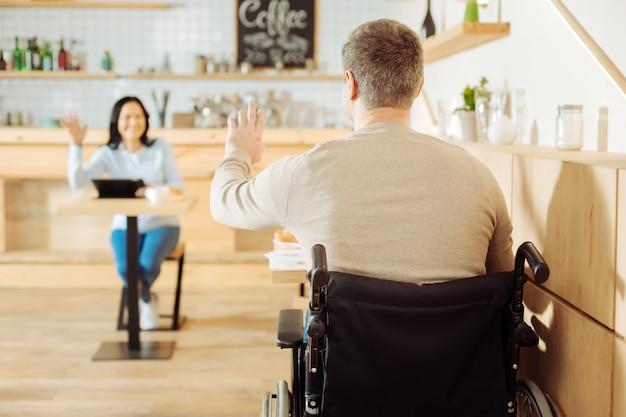 Louro robusto e deficiente, sentado à mesa de um café e acenando para uma mulher sorridente sentada à sua frente