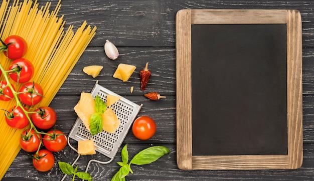 Lousa ao lado de ingredientes para esparguete