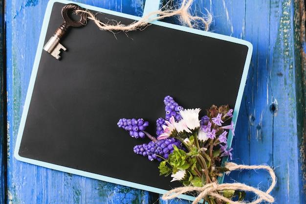 Lousa com flores e chave