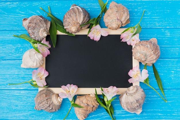 Lousa com folhas de plantas e flores na mesa