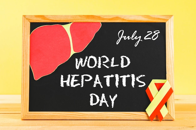 Lousa com texto dia mundial da hepatite. 28 de junho. fita amarela vermelha e fígado