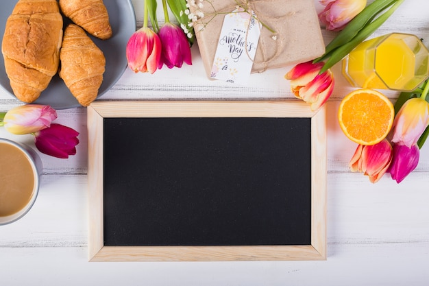 Lousa de quadro e café da manhã clássico com tulipas