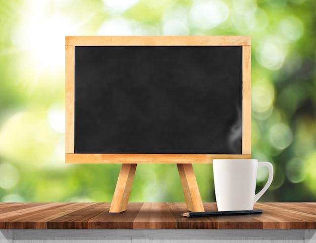 Lousa em branco com cavalete no topo de mesa de madeira marrom com sol e blur bokeh árvore verde