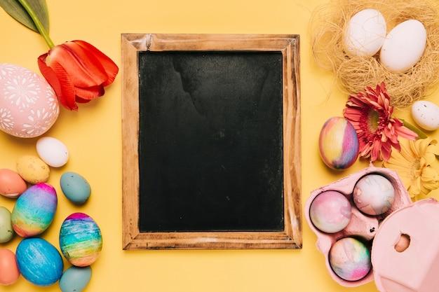Lousa em branco com flores frescas e ovos de páscoa decorados no pano de fundo amarelo