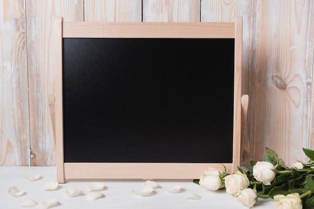 Lousa em branco com lindas rosas na mesa de madeira branca