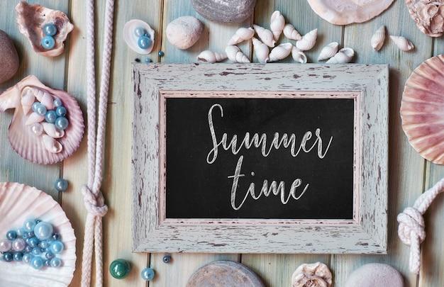 Lousa em branco com texto horário de verão, conchas do mar, corda e peixe estrela em pranchas de madeira verde menta pálida
