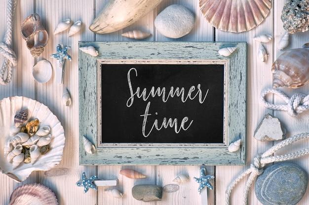 Lousa em branco com texto horário de verão, conchas do mar, corda e peixe estrela na madeira branca