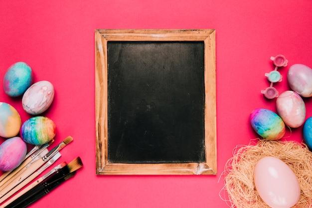Lousa em branco de madeira com ovos de páscoa; pincéis e tinta cor no pano de fundo rosa