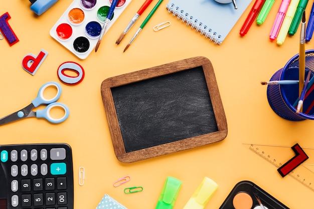 Lousa em branco, rodeada de material escolar, espalhados na mesa amarela