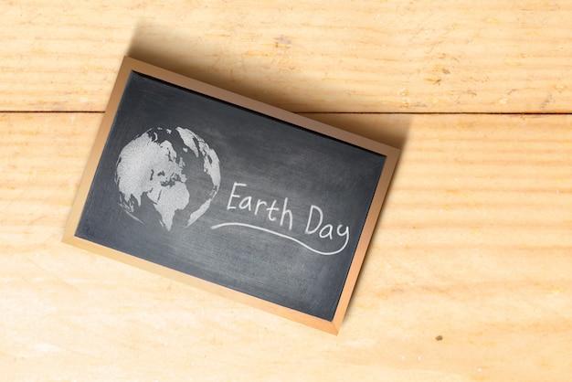 Lousa pequena com mensagem do dia da terra na mesa de madeira