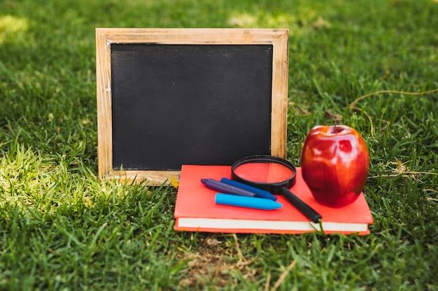 Lousa pequena e papelaria com maçã na grama