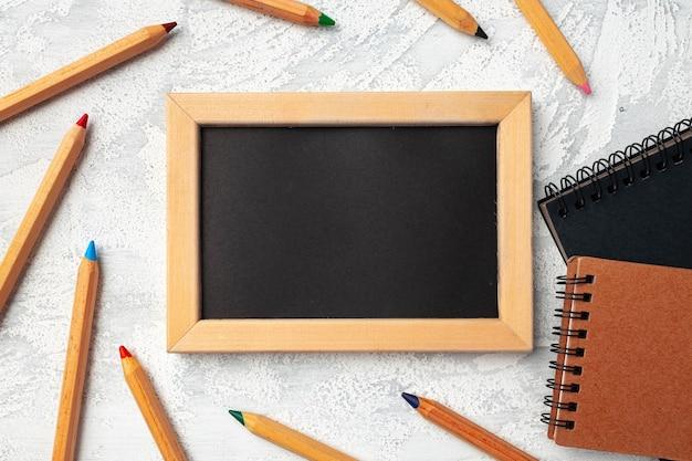 Lousa pequena em moldura de madeira cercada por lápis de cor