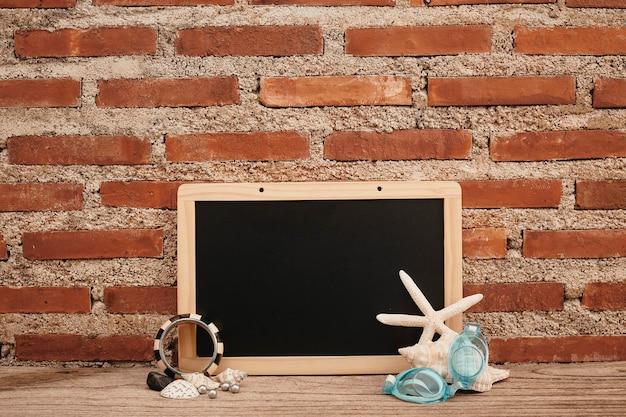 Lousa vazia na mesa de madeira e parede de tijolos, moluscos e copos de mergulho copiam o espaço para o seu texto ou desenho. vista frontal