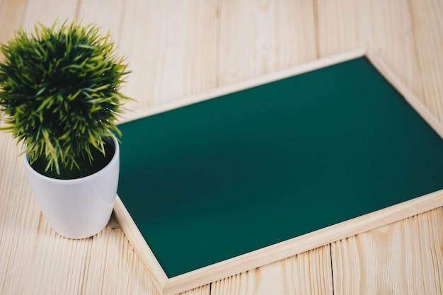 Lousa verde em branco com moldura de madeira e pequena árvore decorativa em vaso branco na mesa de madeira