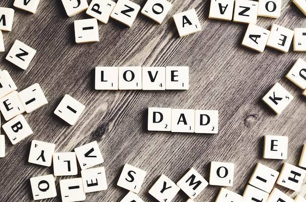 Love dad word em cubos de madeira em um fundo de madeira