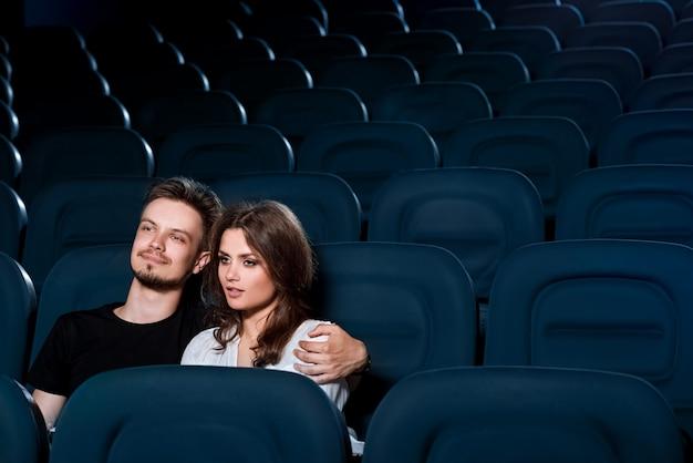 Loving couple assistindo um filme no cinema vazio Foto Premium