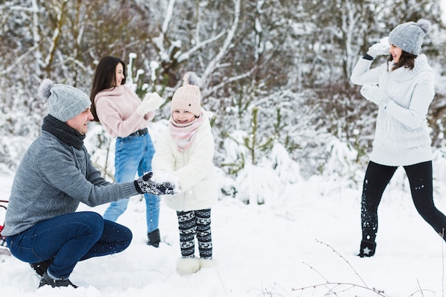 Loving family playing snowballs no campo