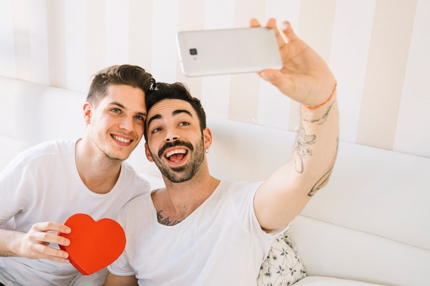 Loving gay couple taking selfie na cama