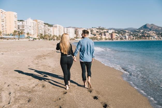 Loving pessoas caminhando na praia de mãos dadas
