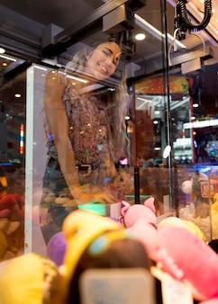 Low view mulher jogando máquina de arcade