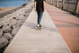 Lowsection vista de um homem andando de skate na parede