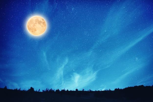 Lua cheia à noite no céu azul escuro com muitas estrelas e nuvens
