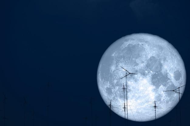 Lua cheia de leite volta em antenas de silhueta no céu noturno