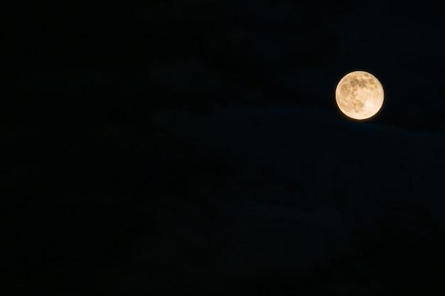 Lua cheia em close-up em um céu negro.