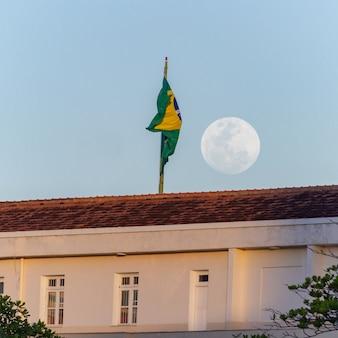 Lua cheia nascendo ao lado da bandeira do brasil no telhado do prédio