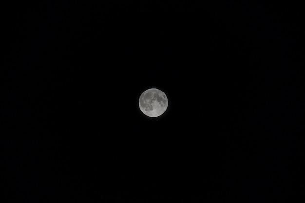 Lua cheia pequena com o céu preto no nighttime.