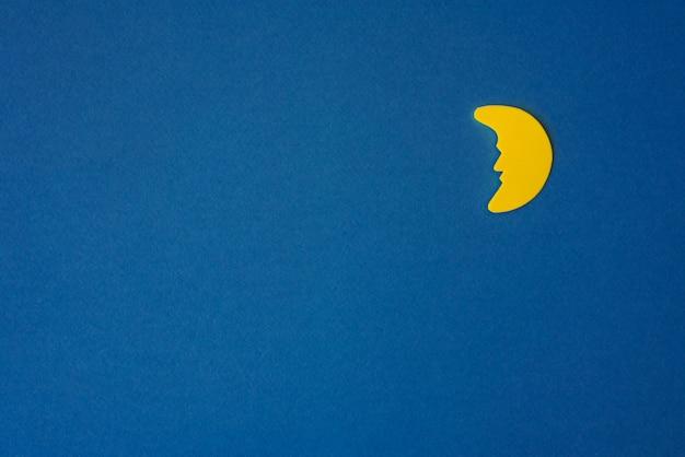 Lua crescente amarela contra o céu noturno azul. papel de aplicação à direita. copie o espaço