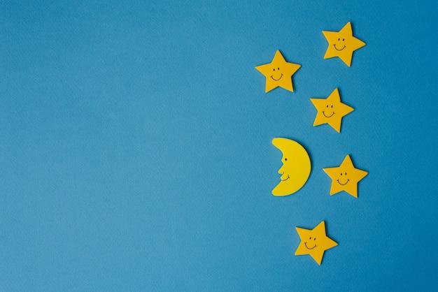 Lua crescente e estrelas amarelas contra o céu noturno azul. papel de aplicação.