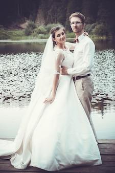 Lua de mel. a noiva e o noivo abraçando na margem do lago.