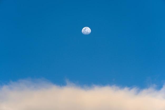 Lua diurna e nuvens estranhas no céu azul