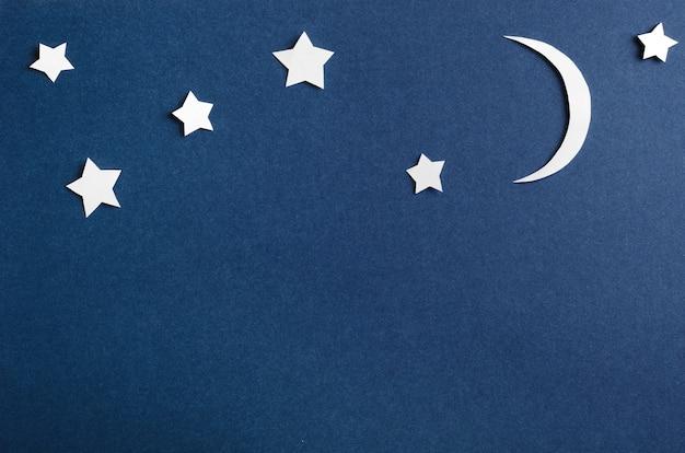 Lua e estrelas na vista superior de fundo azul.