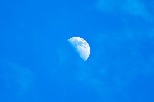 Lua em um céu azul sem nuvens. campo do dia da lua