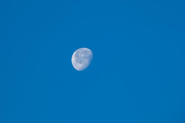Lua jovem no céu azul claro