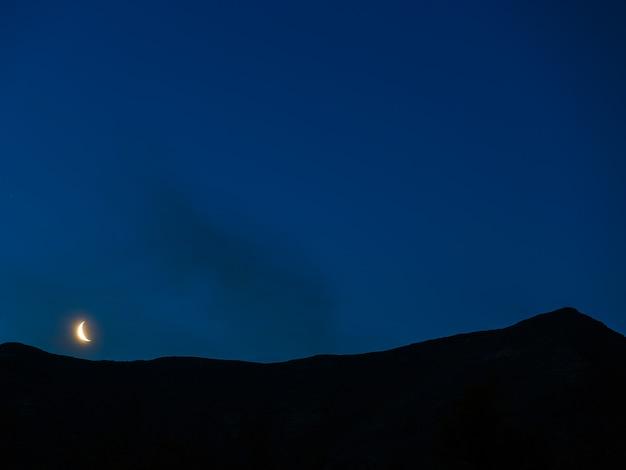 Lua no céu noturno sobre o cume da montanha