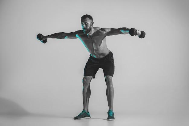 Luar azul. jovem fisiculturista caucasiana treinando sobre fundo de estúdio em luz de néon. modelo masculino musculoso com o peso. conceito de esporte, musculação, estilo de vida saudável, movimento e ação.