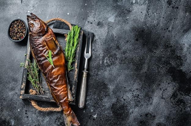 Lúcio ou peixe zander defumado a quente em uma bandeja de madeira. fundo preto. vista do topo. copie o espaço.