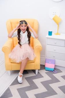 Lugar confortável para descansar. menina sentar cadeira elegante roupa. rosto feliz da menina criança relaxar nas compras. fashionista animada com as compras. crianças boutique salão de roupas de moda. ela é viciada em moda.