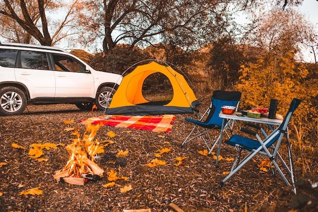 Lugar de acampamento de outono com fogueira e cadeiras portáteis sem pessoas. carro no fundo