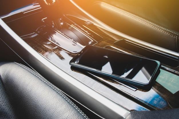 Lugar do telefone inteligente no console do carro em um carro de luxo.