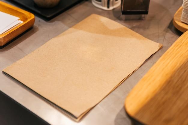Lugar vazio do menu da tampa do papel marrom no balcão da cozinha do café.
