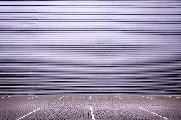 Lugares de estacionamento vazios no fundo de uma parede de metal com espaço para colocação de produtos